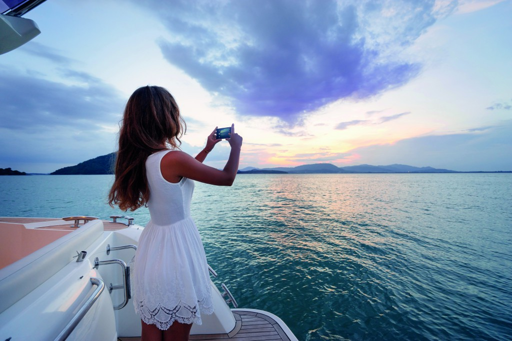 Luxury travel on the yacht. Young woman taking photo of beautiful sea lagoon on smartphone.