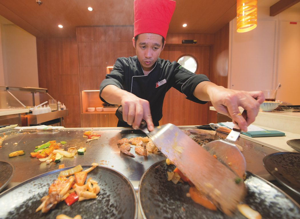 A chef aboard the Carnival Horizon serves entrees to guests during dinner at the Bonsai Teppanyaki that offers a menu of authentic delicacies from the Far East prepared by highly skilled chefs creating dishes on custom-built stations that form the center of the venue's two eight-seat tables. Photo by Andy Newman/Carnival Cruise Line